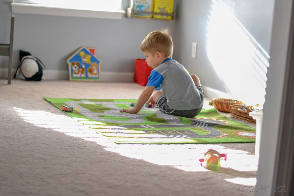 small child playing with toy on play car mat